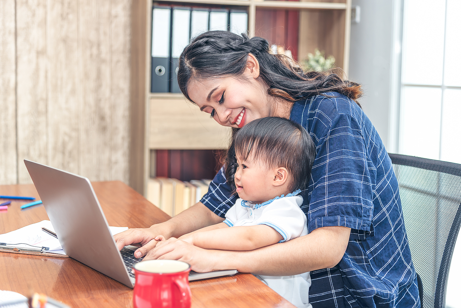 Pretty Young Single Mom Working At Home On A Laptop Computer Whi